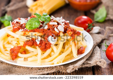 Fresh made Macaroni with Tomato Sauce and Basil on an old wooden table - stock photo