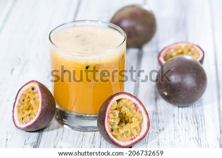 Fresh made Maracuja Juice on wooden background (close-up shot) - stock photo