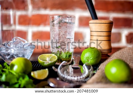 fresh made mint mojito cocktail drink with ingredients at bar - stock photo