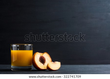 Fresh made peach juice on black wooden background - stock photo