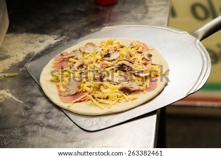 Fresh made pizza on utensil shovel ready to be placed in owen. Photo from real I mean REAL pizza place! - stock photo