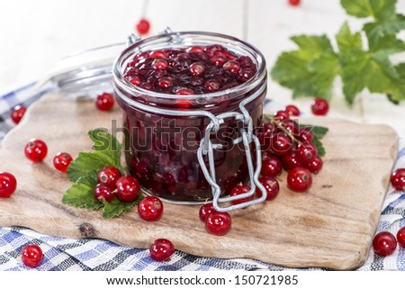 Fresh made Red Currant Jam on wooden background - stock photo