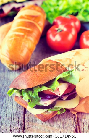 Fresh made sandwich with ham and vegetables.Selective focus on the sandwich - stock photo