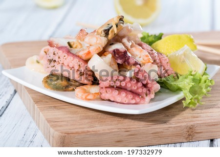 Fresh made Seafood Salad with shrimps, mussels and quid (close-up shot)
