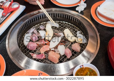 Fresh made squid barbeque in hand - stock photo