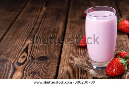 Fresh made Strawberry Milk on an old wooden table (selective focus) - stock photo
