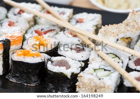 Fresh made Sushi with chopsticks (macro shot) - stock photo