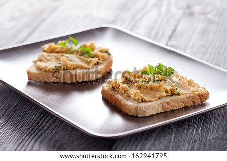 Fresh made toasts with chickpeas hummus served with parsley leaf. Vegetarian breakfast.