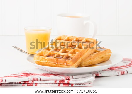 Fresh made waffles and maple syrup served with juice and coffee. - stock photo