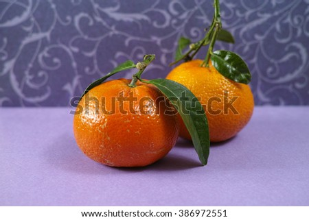 Fresh mandarin oranges fruit with green leaves on purple background - stock photo