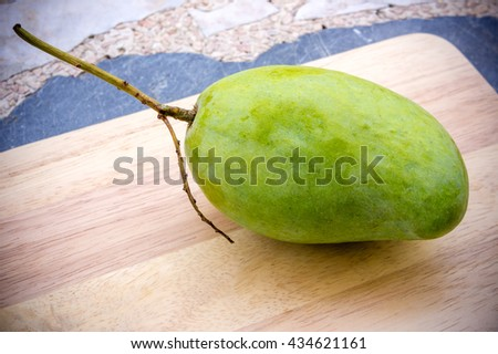 Fresh Mango tropical fruit on beautiful wood board and rock texture plate.
