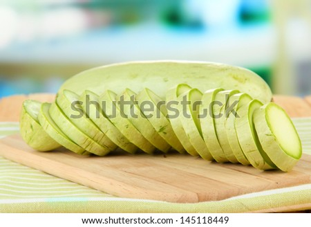 Fresh marrows on cutting board, on wooden table, on bright background