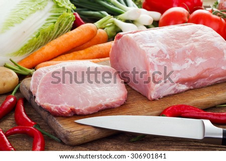 Fresh meat and vegetables on kitchen board - stock photo