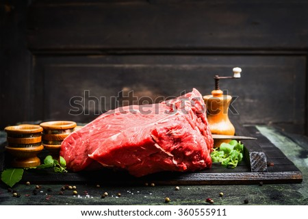 Fresh meat for tasty cooking on rustic kitchen table over dark wooden background, side view - stock photo