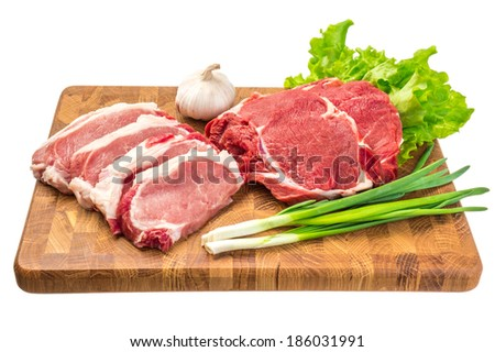 Fresh meat on a wooden board with spices isolated on white background