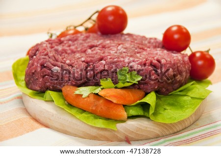 Fresh meat on the table with vegetables. - stock photo