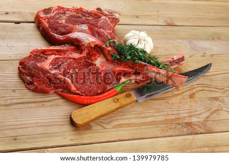 fresh meat : raw beef spare ribs with thyme , garlic and red chili pepper over wooden table - stock photo