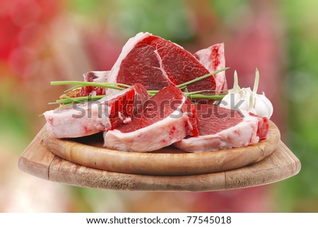 fresh meat : raw uncooked fat lamb pork rib and fillet with green stuff and red chili pepper on wooden plate isolated over white background - stock photo