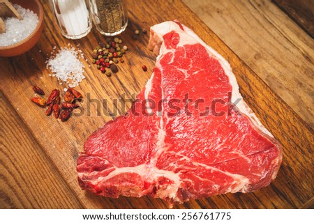 Fresh meat steak with spices on a wooden rustic table - stock photo