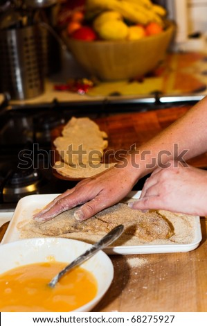 Fresh meat with flour and crumb on in with the hands of a cook with blurry background