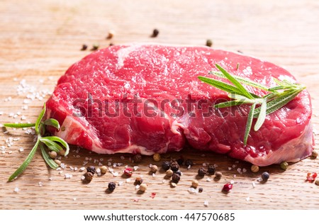 fresh meat with rosemary on wooden board - stock photo