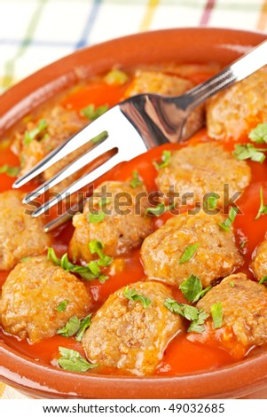 Fresh meatballs in tomato sauce with peas on tablecloth