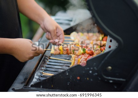 fresh meats in hands prepare in skewer of roaster grill, ready in stove for barbecue party