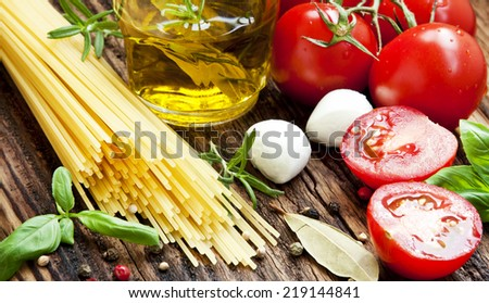 Fresh Mediterranean Ingredients, Spaghetti, Mozzarella, Basil, Olive Oil, Tomatoes and Spices for Italian Cooking Recipe on Wooden Background - stock photo