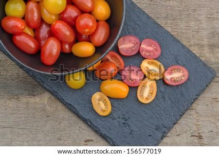 Fresh Meli Melo Heirloom tomatoes in rustic setting - stock photo