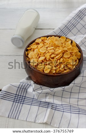Fresh milk and cornflakes in a wood bowl on a wooden table and napkin. Organic healthy food rich in minerals and vitamins. Eco food for breakfast. - stock photo