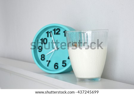Fresh milk in glass with green clock for refresh in morning - stock photo