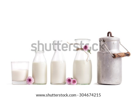 fresh milk in old fashioned bottles in rustic Setting, isolated on white - stock photo