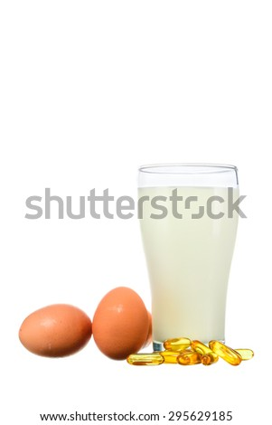 Fresh milk in the glass with egg and vitamin D on white background