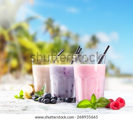 Fresh milk, raspberry, banana and blueberry drinks on wooden table, assorted protein cocktails with fresh fruits. Natural background. Tropical beach, sea, summer concept. - stock photo