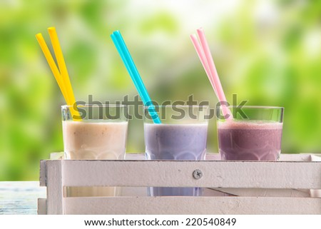 Fresh milk, raspberry, blueberry and vanilla drinks on wooden table, assorted protein cocktails with fresh fruits and nature background. Healthy lifestyle.
