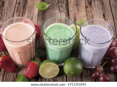 Fresh milk shake, strawberry, lime and grape wooden background, assorted protein cocktails with fruits.  - stock photo