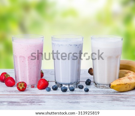 Fresh milk, strawberries, blueberry and banana drinks on wooden table, assorted protein cocktails with fresh fruits. Healthy lifestyle.  - stock photo