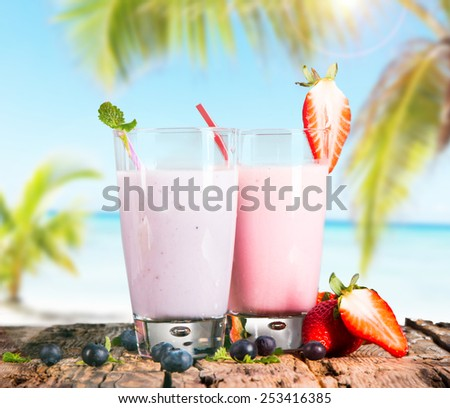 Fresh milk, strawberry and blueberry banana drinks on wooden table, assorted protein cocktails with fresh fruits and tropical beach background. - stock photo