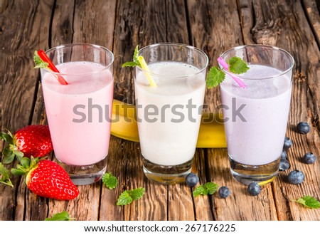 Fresh milk, strawberry, blueberry and banana drinks on woden table, assorted protein cocktails with fresh fruits. - stock photo