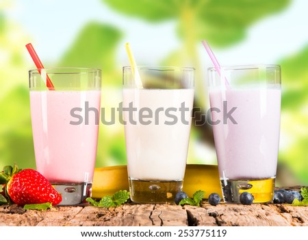 Fresh milk, strawberry, blueberry and banana drinks on wooden table, assorted protein cocktails with fresh fruits and nature green background. - stock photo
