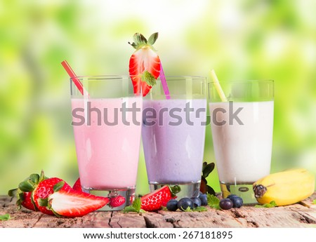Fresh milk, strawberry, blueberry and banana drinks on wooden table, assorted protein cocktails with fresh fruits.
