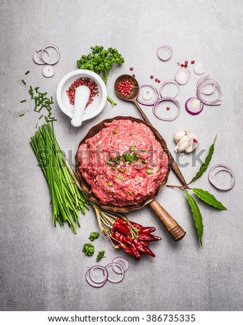 Fresh Minced meat  with green seasoning and ingredients for tasty cooking on  gray stone background, top view composing. - stock photo