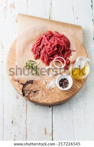 Fresh minced meat with onion and spices on wooden cutting board on blue background - stock photo