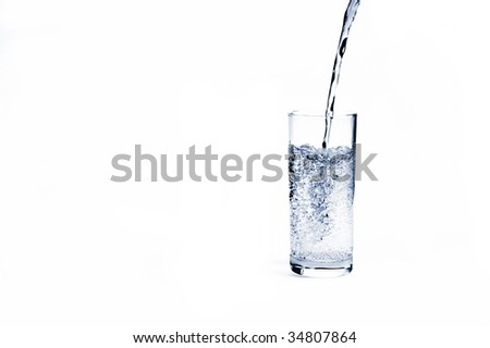 Fresh mineral water stream pouring into glass with bubbles - stock photo