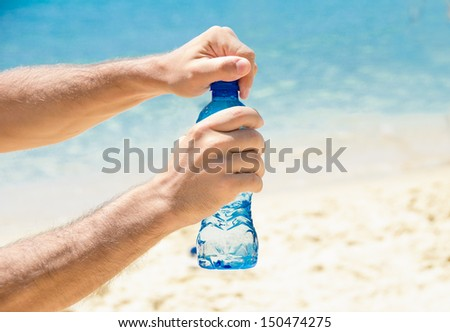 Fresh mineral watter suggested by two hands opening a bottle on a hot summer day at the beach - stock photo