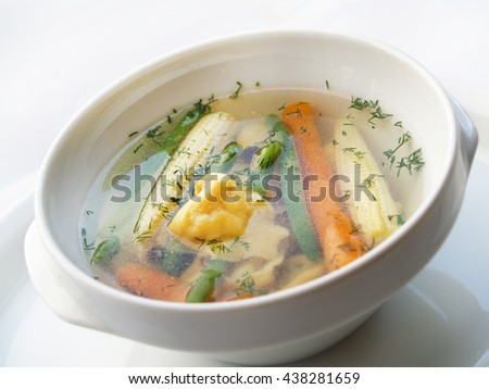 fresh minestrone soup with corn, carrots, dumplings and herbs.