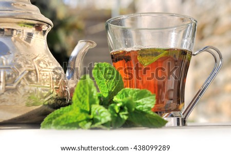 fresh mint and tea with oriental teapot on a table garden  - stock photo