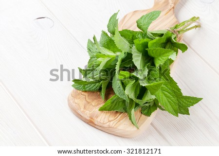 Fresh mint bunch on cutting board. Top view with copy space - stock photo