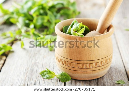 Fresh mint in wooden mortar on grey wooden background - stock photo