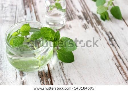 fresh mint oil in  bottle on wooden boards - stock photo